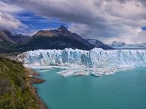 An angry sky over a blue glacial lake stock photo