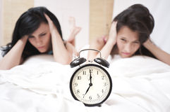 Angry sleeping women looking at a ringing clock. Angry sleeping women on white steets looking stressed a ringing clock in the morning royalty free stock photo