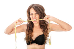 Angry slim girl biting a measuring tape Royalty Free Stock Photography