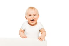 Angry small baby with open mouth in white bodysuit Stock Photo