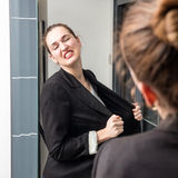 Angry smart young woman losing temper in front of her mirror Stock Photography