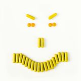 Angry smile made from many pills and capsules. wellness concept Stock Photography