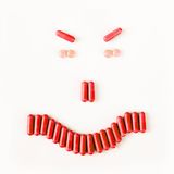 Angry smile made from many pills and capsules. wellness concept Royalty Free Stock Photos
