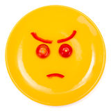 Angry smiley face made on plate Royalty Free Stock Images