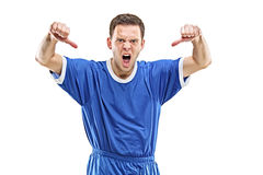 An angry soccer player shouting. And giving thumbs down isolated on white background Royalty Free Stock Photo