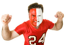 Angry Sports Fanatic. Angry sports fan with a painted face, raising his fists and growling aggressively Stock Image