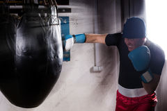 Angry sporty boxer with stern look in a hat and boxing gloves. Training with boxing punching bag in a gym Royalty Free Stock Image