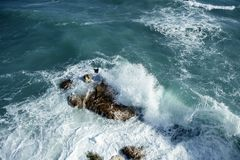 Angry stormy sea waves reaching a big stone Royalty Free Stock Photo