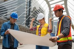Angry American engineer female boss at site. Angry and stress American women boss look at blueprint paper plan and blame Asian engineering men team for project Stock Photo