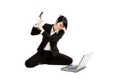 Angry and stressed businesswoman. An angry and stressed businesswoman is about to smash a laptop with a hammer Royalty Free Stock Photography