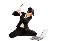 Angry and stressed businesswoman. An isolated shot of an angry and stressed businesswoman smashing her laptop with a hammer Royalty Free Stock Image