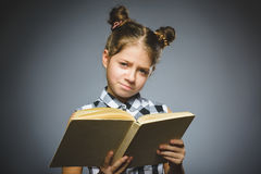 Angry or stressed girl with book. child on grey background. studies concept royalty free stock photo