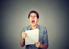Angry stressed screaming business man with documents papers paperwork. Isolated on gray office wall background. Negative emotions face expression Stock Photo