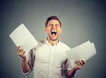 Angry stressed screaming business man with documents papers. Paperwork isolated on gray wall background. Negative emotions face expression stock image