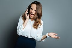 Angry stressed woman shouting at her interlocutor. Bad mood. Moody stressed unhappy woman holding her phone and shouting at her interlocutor while being very Royalty Free Stock Photography