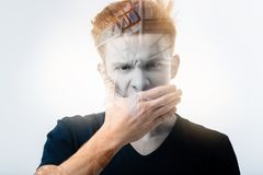 Angry stressful man holding hand near mouth and looking straight. Keep silence. Angry stressful redhead man standing in the room holding hand near mouth and Stock Image