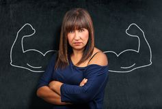 Angry and strong brunette woman at blackboard or chalkboard show stock photography