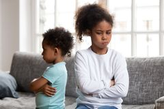 Angry stubborn african sister and offended brother ignoring each. Angry stubborn african preschool girl sister and offended little boy brother ignoring each stock photography
