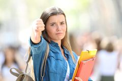 Angry student gesturing thumbs down. Looking at camera in the street Royalty Free Stock Image