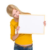 Angry student girl biting blank board. Isolated on white royalty free stock photography