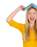 Angry student girl with book over head Royalty Free Stock Photo