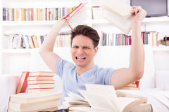 Angry student  surrounded by books  throws books Royalty Free Stock Photos