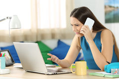Angry student talking on phone with customer service. Angry student looking at a laptop and consulting on phone with customer service in her bedroom in a house Stock Image