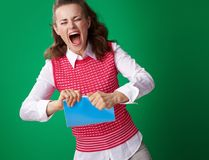 Angry student woman tearing blue notebook on green background Stock Image