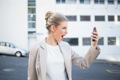 Angry stylish businesswoman shouting at her phone. Outdoors on urban background Royalty Free Stock Photos