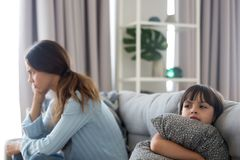 Angry sulky child and annoyed mother not talking after fight. Angry sulky child girl and annoyed mother sitting back to back on sofa not talking after fight royalty free stock photo