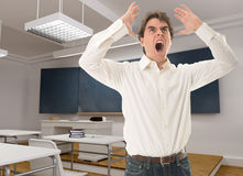 Angry teacher. In a classroom royalty free stock image