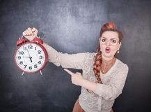 Angry teacher with clock on the chalkboard background stock images