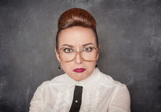 Angry teacher with eyeglasses. On the school blackboard background royalty free stock image