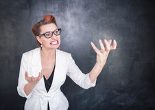 Angry teacher in glasses on blackboard background. Angry teacher in glasses on chalkboard blackboard background stock photos