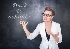 Angry teacher in glasses on chalkboard background stock photos