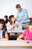Angry Teacher Looking At Student. Angry mature teacher standing arms crossed while looking at student during examination in classroom Stock Photo