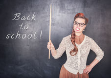 Angry teacher with pointer on blackboard background Royalty Free Stock Photos
