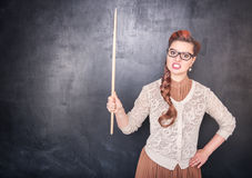 Angry teacher with pointer on blackboard background Royalty Free Stock Images