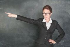 Angry teacher pointing out. Angry teacher in glasses pointing out stock photography