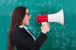 Angry teacher shouting through megaphone Royalty Free Stock Photography