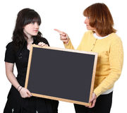 Angry Teacher and Student. Angry school teacher and highschool student holding chalkboard Stock Photography