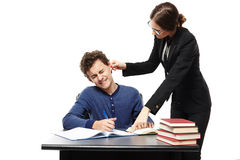 Angry teacher twisting the student's ear and pointing him someth. Studio shot of angry teacher twisting the student's ear and pointing him something in his royalty free stock photos