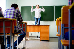 Angry teacher yelling. Angry female teacher is yelling at students royalty free stock photo