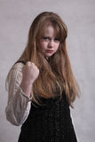 Angry teen blonde girl. Teen blonde girl clenching a fist in anger royalty free stock images