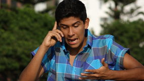 Angry Teen Boy Talking On Cell Phone Stock Photography