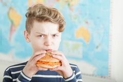 Angry teen boy trying to eat a carrot burger. Close up on single angry teen boy trying to eat a burger full of carrot shreds while standing in front of map Royalty Free Stock Photography