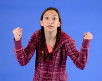 Angry teen girl with braids with fists up. Teen girl with angry expression holding her fists up while staring defiantly with big eyes Stock Images