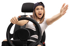Angry teenage driver holding a steering wheel. And gesturing with her hand isolated on white background Royalty Free Stock Photos