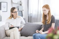 Angry girl sitting in psychotherapy royalty free stock photo