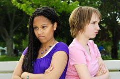Angry teenage girls. Two unhappy teenage girls sitting on bench Stock Image
